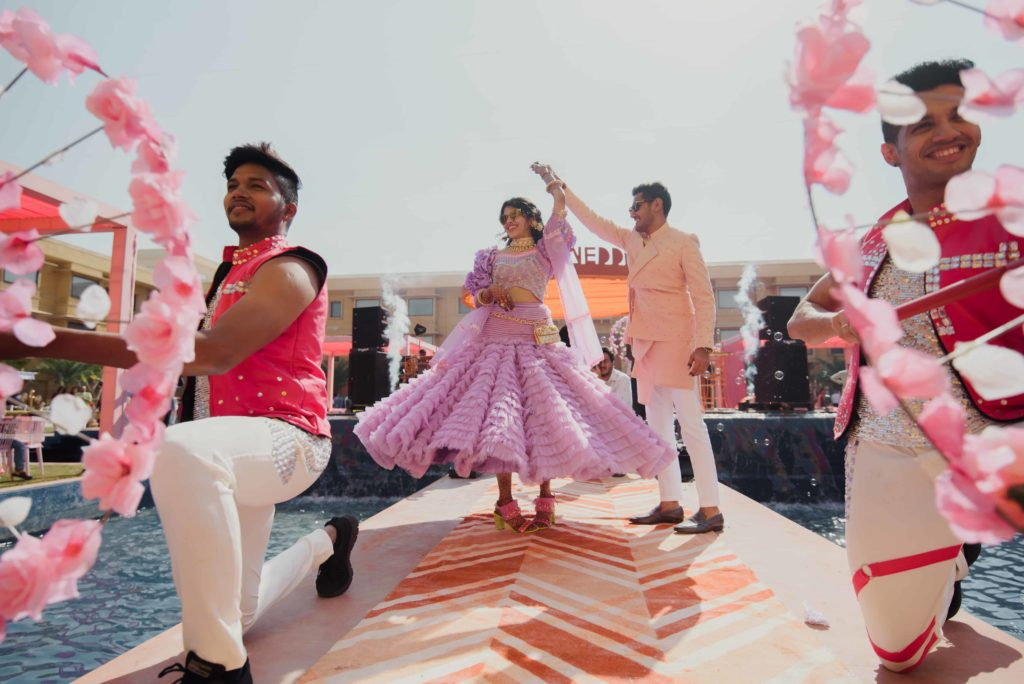 Indian bride and groom dancing wedus